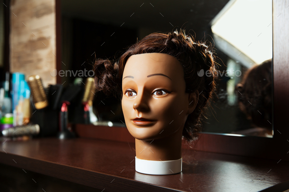 Hairdressing mannequin located on a wooden table. - Stock Photo - Images