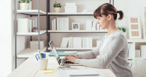 Young office worker working at desk - Stock Photo - Images