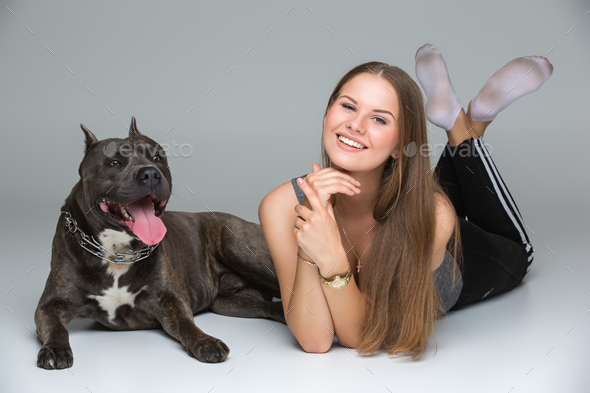 Beautiful girl with grey stafford terrier - Stock Photo - Images