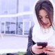 Young Brunette Woman Sits Outside With Her Phone - VideoHive Item for Sale