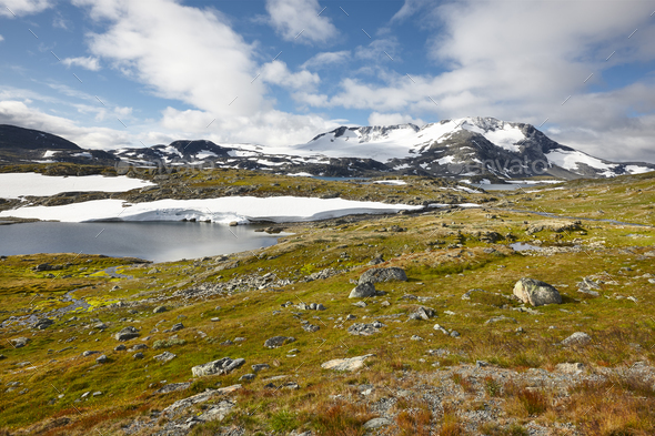 Norwegian rocky mountain landscape with lakes and snow. Norway trekking. Horizontal - Stock Photo - Images
