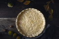 Raw shortcrust pastry in the baking dish on the wooden table top view
