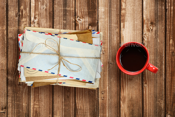 Pile of old envelopes and coffee cup on wooden table top view - Stock Photo - Images