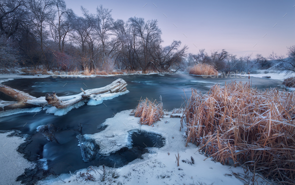 Winter landscape with snowy trees, beautiful frozen river at dus - Stock Photo - Images