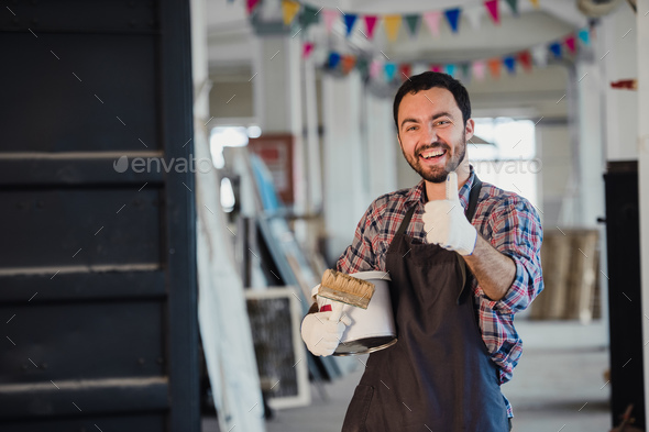 Handyman using brush in his workshop with thumb up - Stock Photo - Images