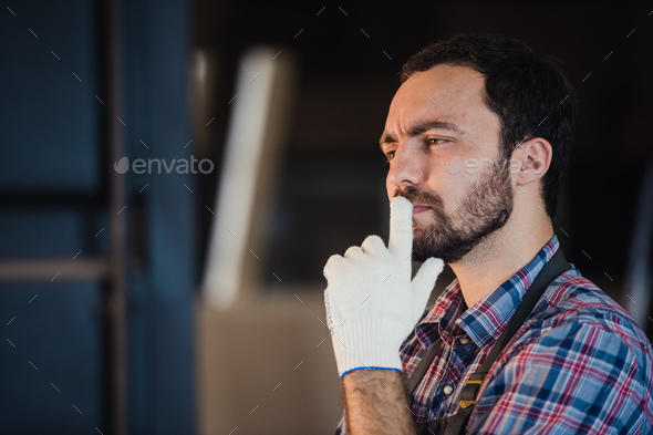 Thoughtful carpenter wearing gloves in his workshop - Stock Photo - Images