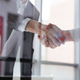 Download Two businessmen standing and shaking hands in office from PhotoDune