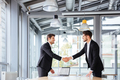 Two happy businessmen standing and shaking hands on business meeting - PhotoDune Item for Sale