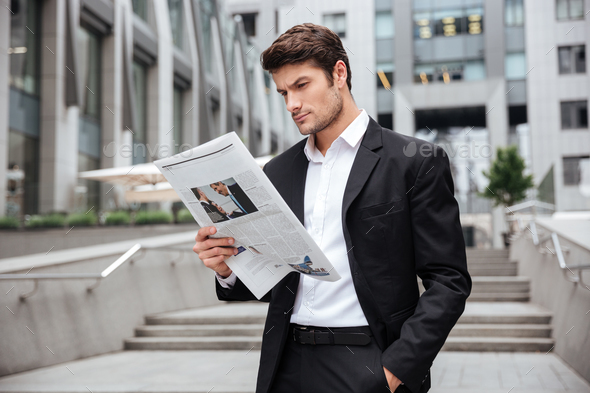 Businessman standing and reading newspaper outdoors - Stock Photo - Images