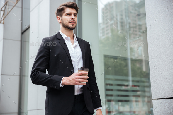 Businessman walking and drinking coffee outdoors - Stock Photo - Images