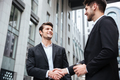 Two cheerful young businessmen shaking hands - PhotoDune Item for Sale