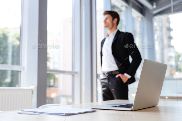 Businessman with laptop and documents standing near the window - Stock Photo - Images