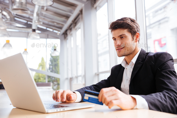 Businessman using laptop and credit card at the table - Stock Photo - Images