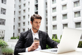 Businessman working with laptop and drinking coffee outdoors