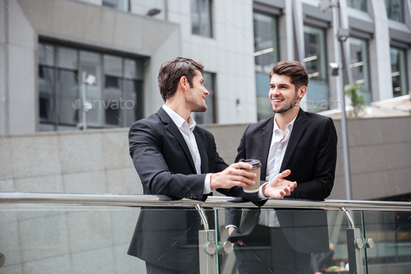 Two businessmen talking and drinking coffee in the city - Stock Photo - Images