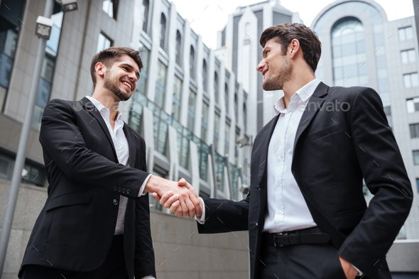 Two happy businessmen standing and shaking hands near business center - Stock Photo - Images