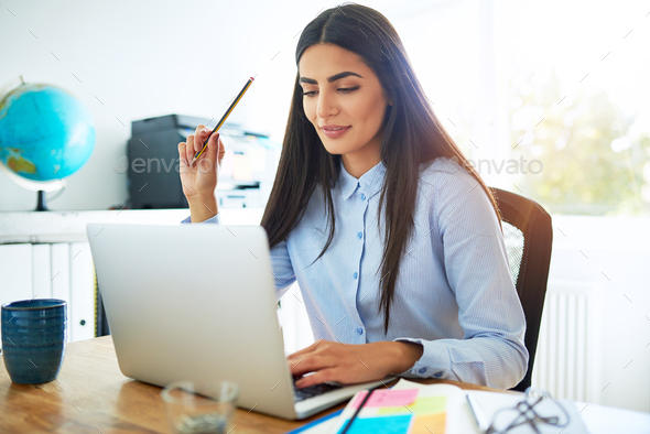 Thoughtful young Indian woman holding pencil - Stock Photo - Images