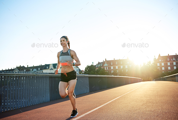 Athletic young woman enjoying a morning run - Stock Photo - Images