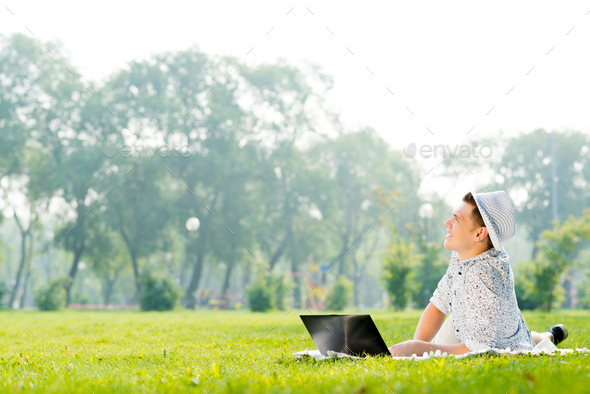 young man working in the park with a laptop - Stock Photo - Images