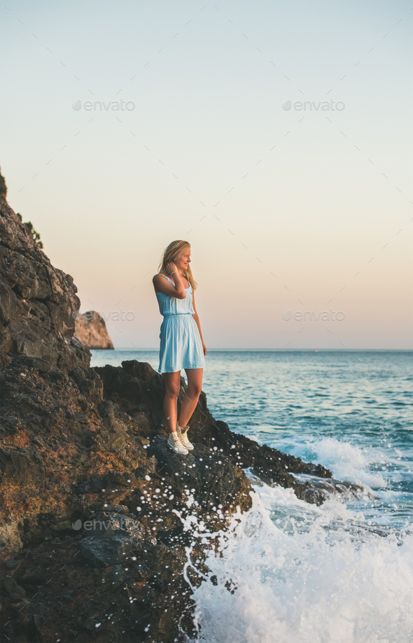 Young blond woman looking at horizon and smiling, Alanya, Turkey - Stock Photo - Images
