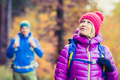 Man and woman happy couple hikers walking in autumn woods
