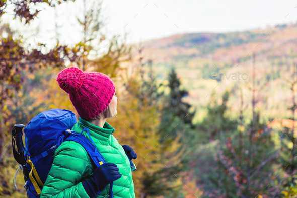 Hiking woman with backpack looking at inspirational autumn golde - Stock Photo - Images