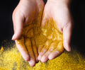 Golden glitter sand in hands on black, abstract background.