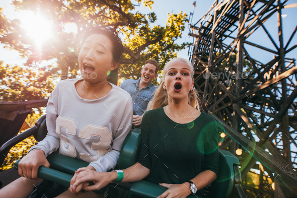 People enjoying a ride in amusement park - Stock Photo - Images