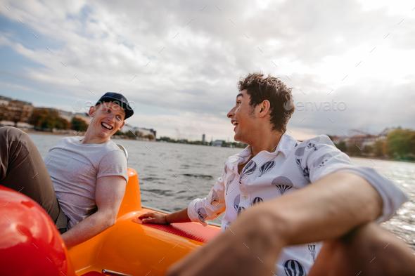 Teenage boys enjoying boating in the lake - Stock Photo - Images