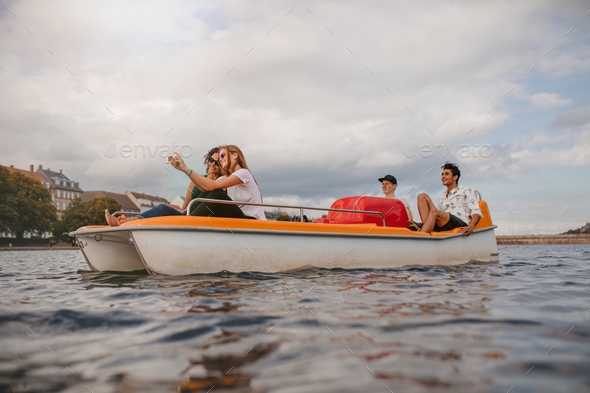 Group of people in boat taking selfie - Stock Photo - Images