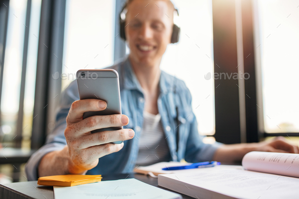 Male student in library using mobile phone - Stock Photo - Images