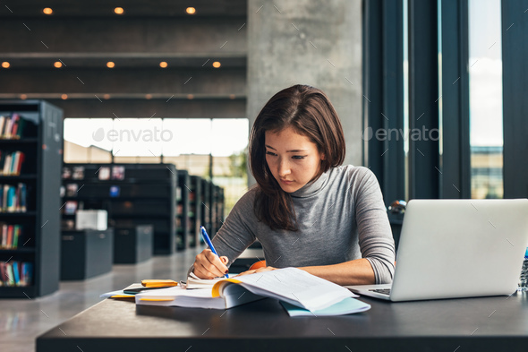 Female student studying at college library - Stock Photo - Images