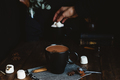 Comforting Mug of Hot Chocolate on Rustic Table with Female Hand Picking Marshmallows in Background Nulled