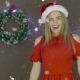 Cute Young Female in Red Dress and Christmas Hat Blowing a Kiss at You on Christmas Background - VideoHive Item for Sale