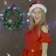 Beautiful Blonde Girl in Red Dress and Christmas Hat Holding a Chalkboard with Inscription Merry - VideoHive Item for Sale