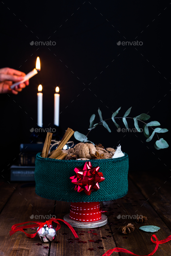 Festive Tin Filled with Nuts on Rustic Table against Candlelit Background - Stock Photo - Images