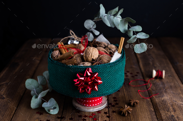 Horizontal View of Christmas Tin filled with Nuts and Spices on Rustic Table - Stock Photo - Images
