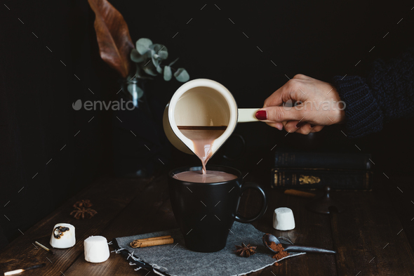 Female Pouring Hot Chocolate Drink from Milk Pan into Black Mug on Rustic Table - Stock Photo - Images