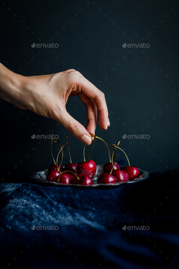 Hand Picking Red Cherries from Silver Platter against Black Background - Stock Photo - Images
