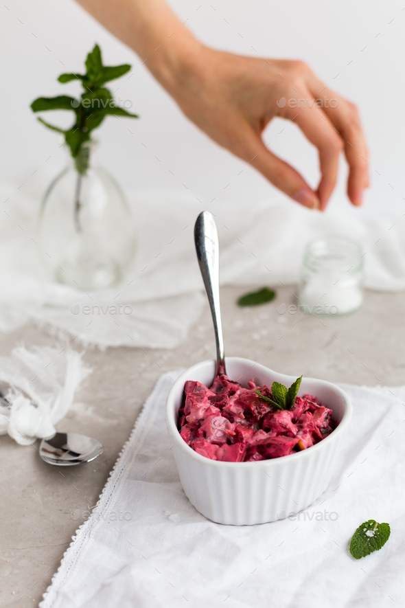 Beetroot Dip in White Dish with Female Hand Seasoning in Background - Stock Photo - Images