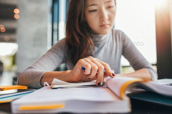 Student doing assignments in library - Stock Photo - Images
