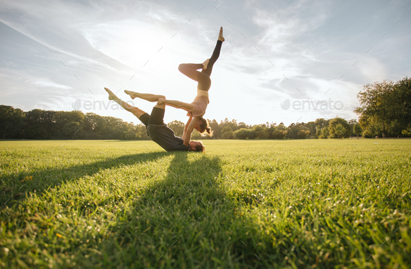 Healthy couple doing acro yoga on grass - Stock Photo - Images