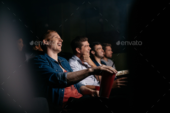 Young people watching comedy movie in theater - Stock Photo - Images