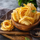 Freshly prepared fettuccine pasta on cutting board. - PhotoDune Item for Sale