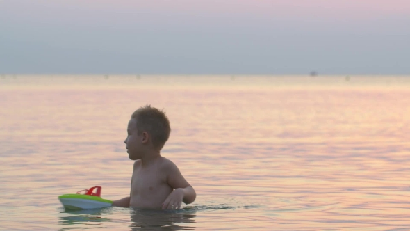 Lillle Boy Toys Boats : Boy playing with toy boat in sea by grey coast media