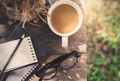 Notebook with cup of coffee on wooden table in the garden