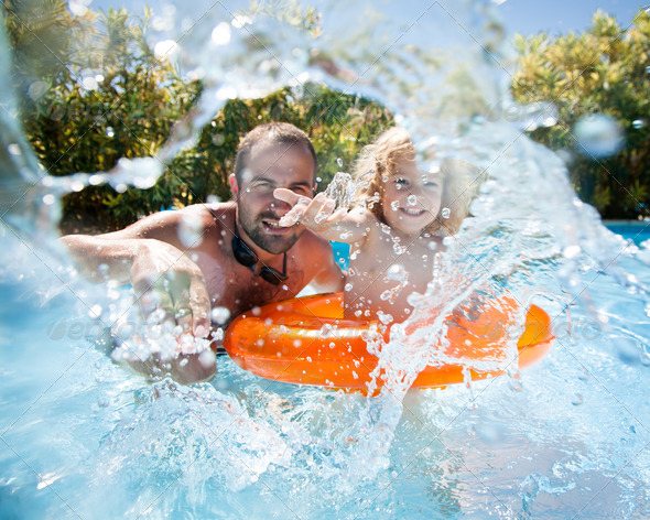 Child with father in swimming pool - Stock Photo - Images