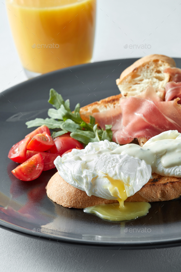 Eggs Benedict with ham and tomato - Stock Photo - Images