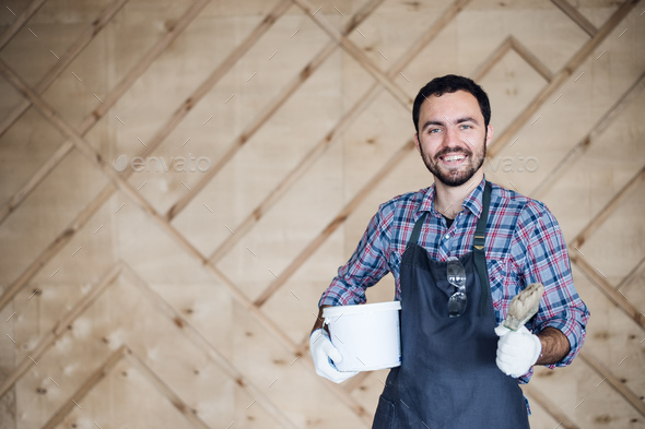 Young male carpenter wearing gloves and glasses with hands on hips - Stock Photo - Images