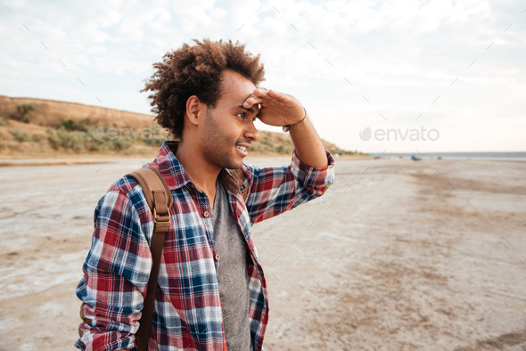 Concentrated african man standing outdoors and looking far away - Stock Photo - Images